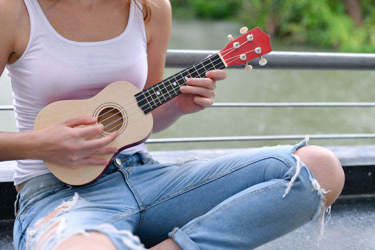 Midsection of woman playing ukulele while sitting by railing