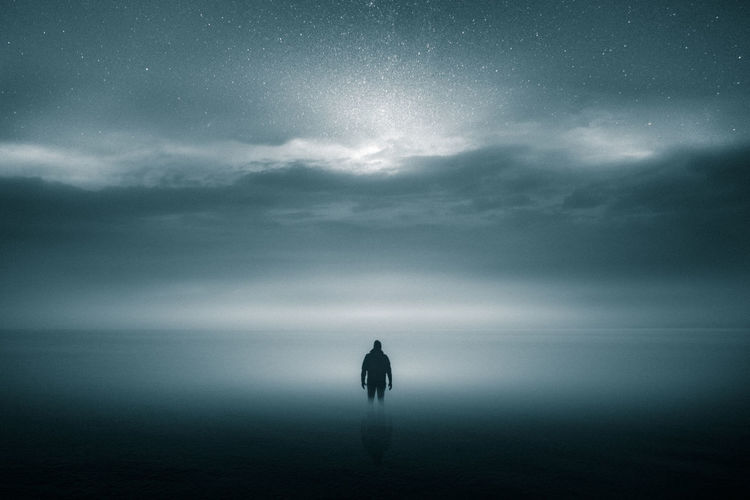 Rear view of silhouette person standing in sea against cloudy sky
