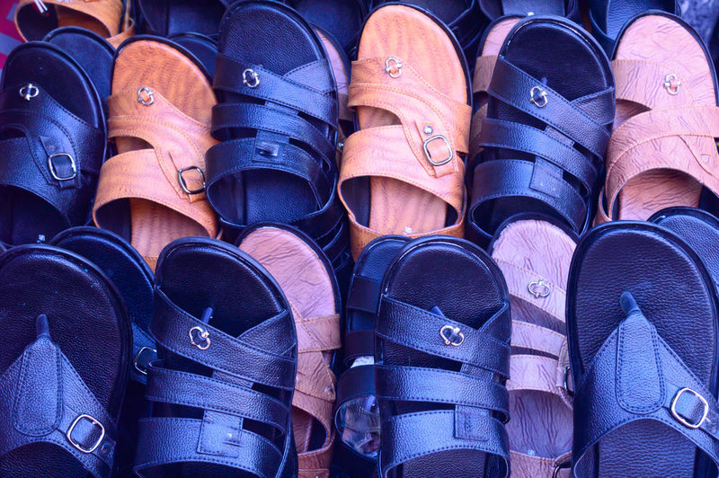 Leather shoe fashion foot ware closeup. Display for sale in a retail market shop. View of Handmade, handicraft, Luxury, colorful fashionable, stylish rubber sandals collection. Traditional formal wear Shoe Blue Large Group Of Objects Choice Variation Side By Side In A Row Arrangement Backgrounds Abundance Close-up Pair Group Of Objects Market Stall Dress Shoe Canvas Shoe Footwear Flat Shoe Things That Go Together Sole Of Shoe Shoelace For Sale Many Menswear Soccer Shoe Various Boot Display Stall Colorful