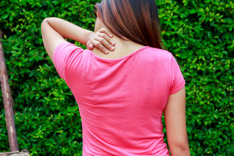 Rear View Of Woman With Neckache Standing Against Plants