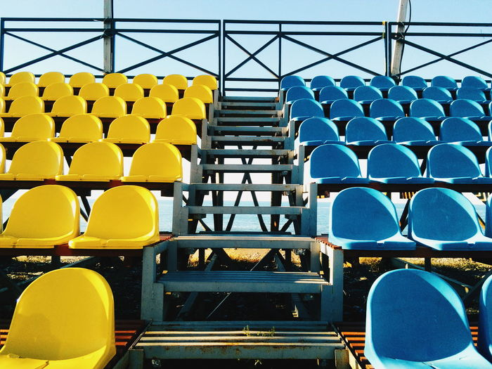 Low angle view of empty yellow and blue seats