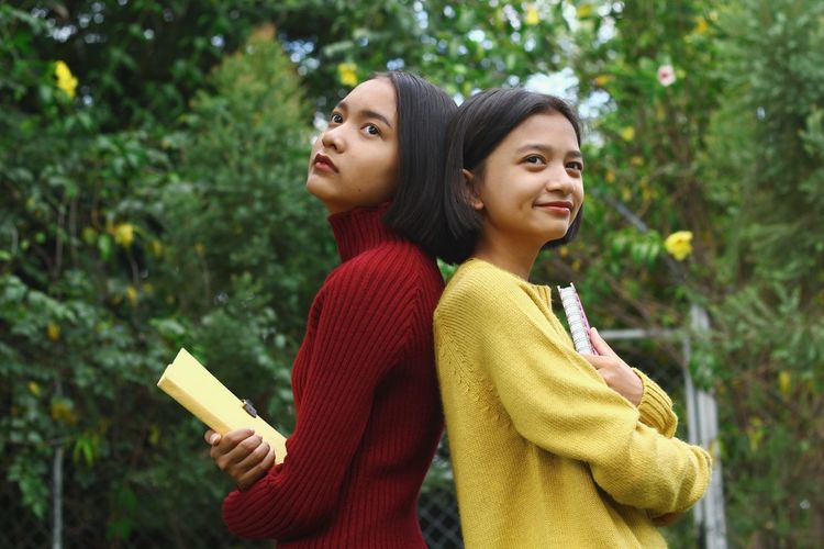 Sisters with back to back standing against trees in park