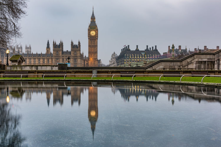 Big ben in city reflecting on water against sky
