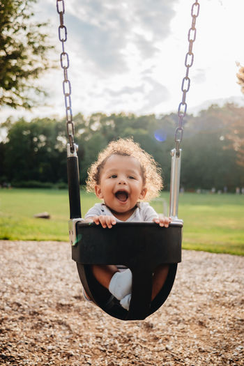 Portrait of boy on swing in playground