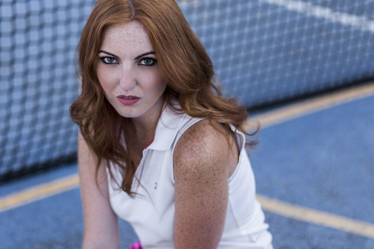 Portrait of a beautiful woman sitting on playing field