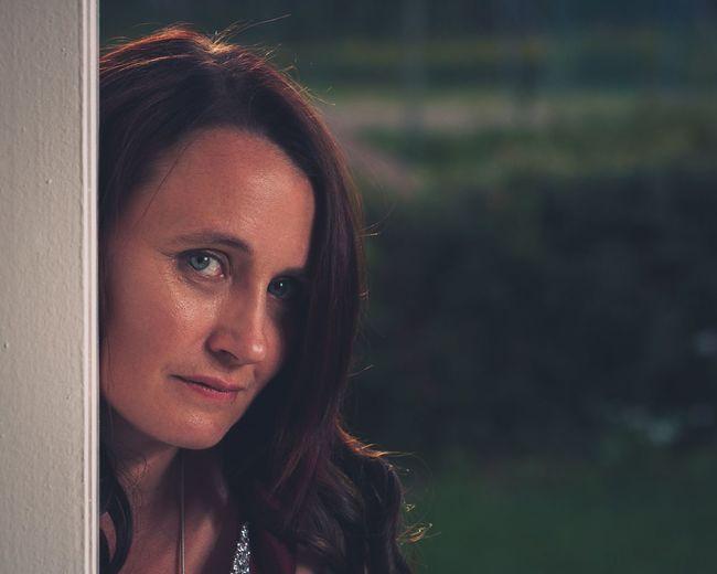 Close-up portrait of mature woman peeking from door