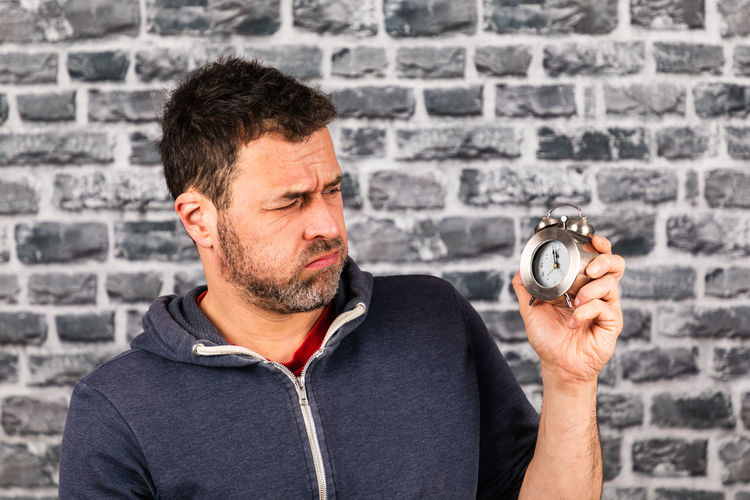 Midsection of man holding clock against wall