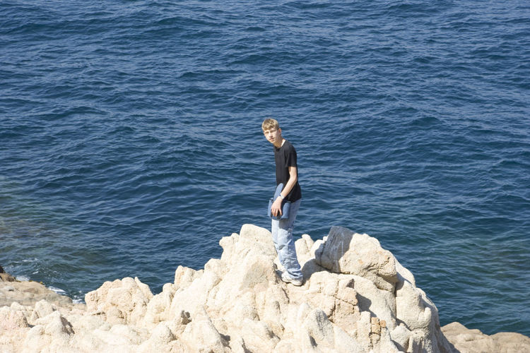 Full length of man standing on cliff by sea during sunny day