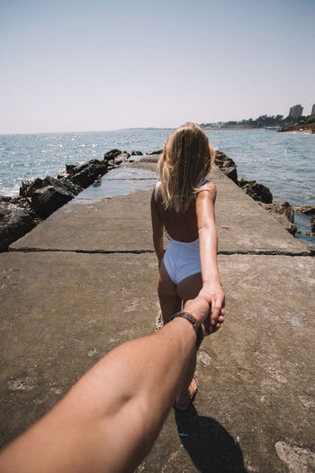 Rear view of woman holding hand of boyfriend by sea on pier