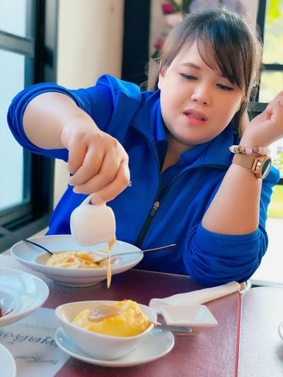 Midsection of girl holding food on table