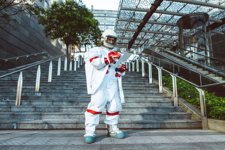 Full length of astronaut standing in front of staircase outdoors