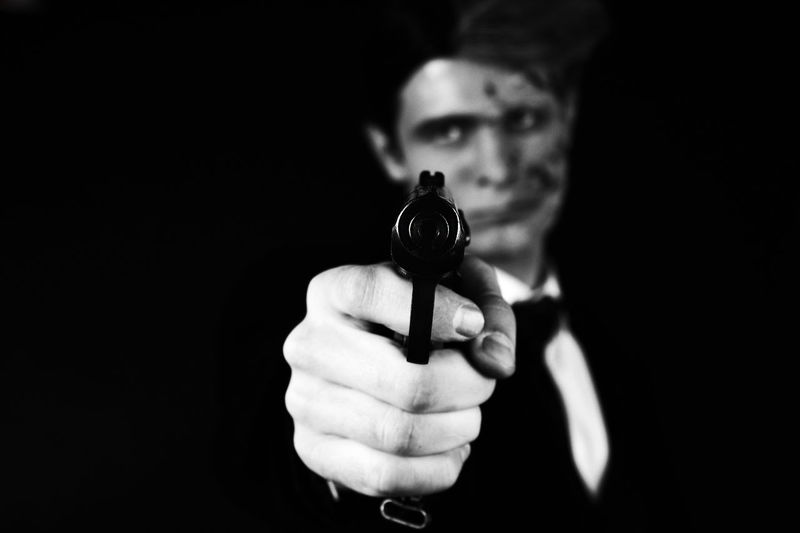 Portrait Of Young Man In Costume Aiming Gun Against Black Background