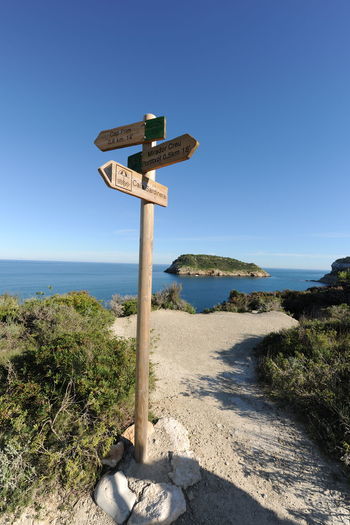 Sign board by sea against clear blue sky