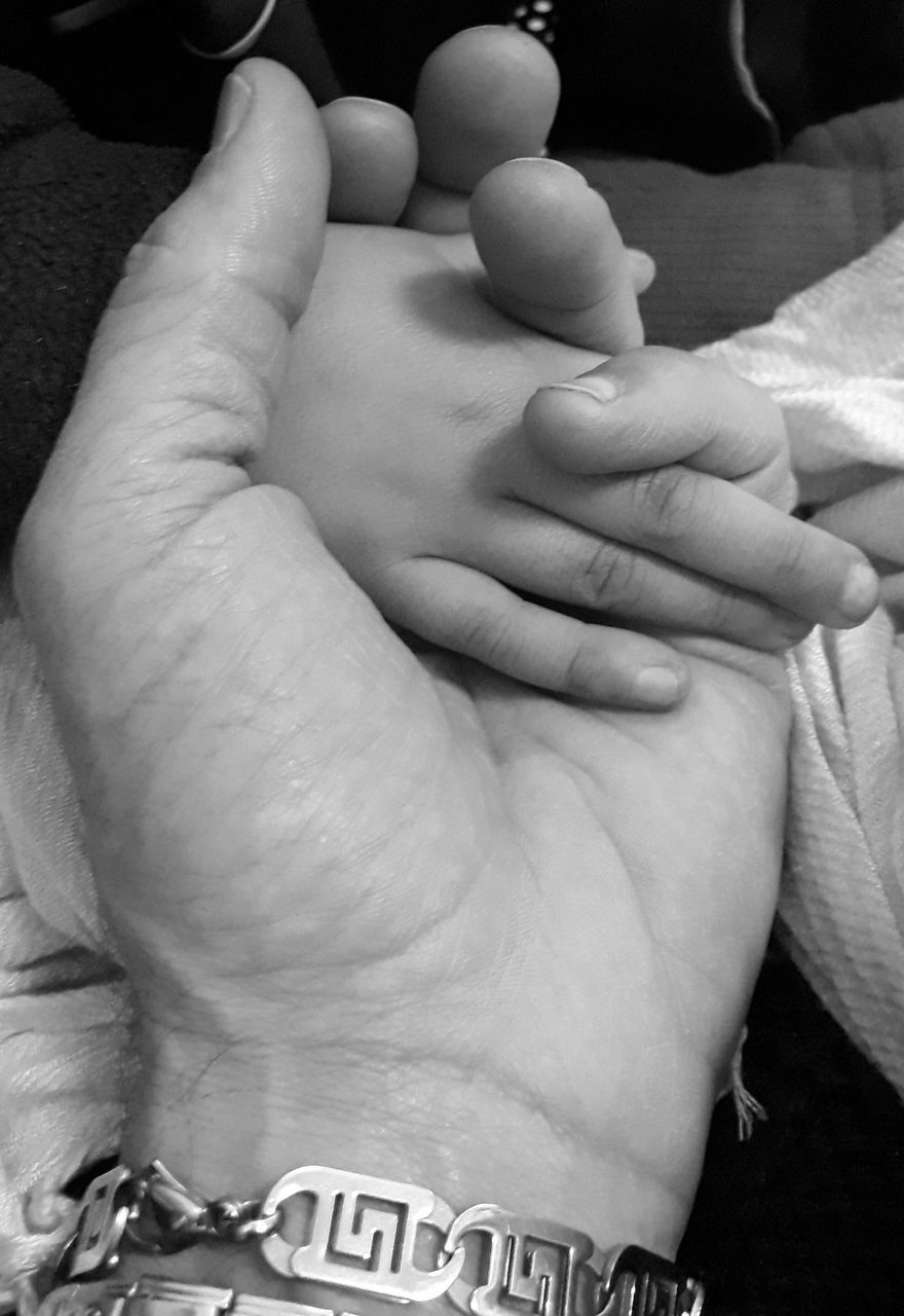 human body part, real people, togetherness, human hand, baby, human finger, love, bonding, two people, family, men, babyhood, newborn, indoors, leisure activity, close-up, care, lifestyles, women, childhood, fragility, day, adult, people