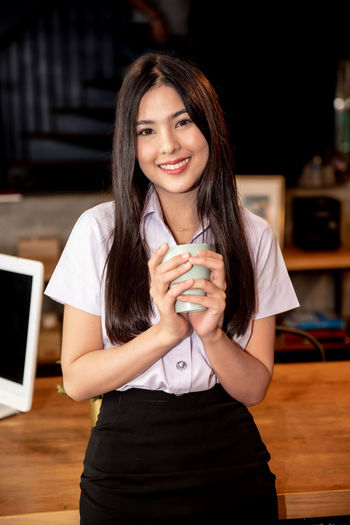 Portrait of smiling young woman using smart phone on table