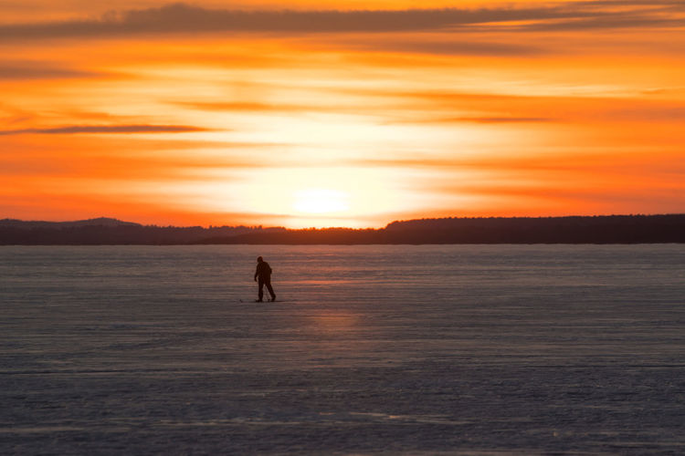 Sky Ski Skiing Scenics - Nature Beauty In Nature Tranquility Tranquil Scene Nature Canada Coast To Coast Orange Color Orange Orange Sky Sunset Silhouette One Person Water Real People Lifestyles Leisure Activity Waterfront Sea Land Sport Cold Temperature Outdoors