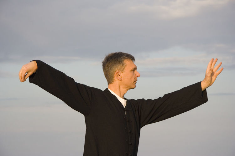 Mid adult man practicing tai chi against sky