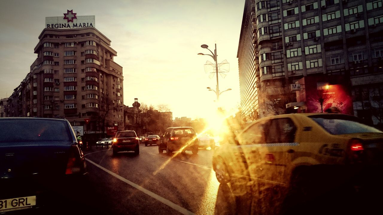 Cars Moving On Road Against Sky In City During Sunset
