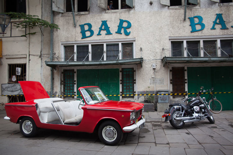 Red Vintage Car On Street In Front Of Building