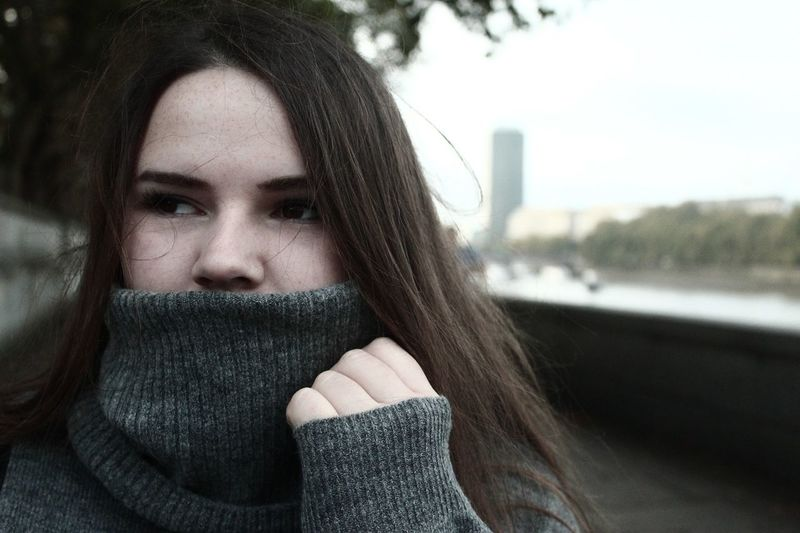 Close-Up Of Thoughtful Young Woman Wearing Warm Clothing In City