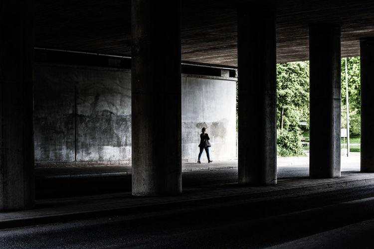 Rear view of silhouette woman walking under bridge