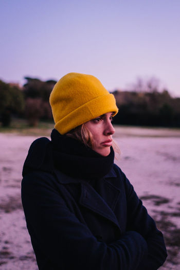 Young woman in hat looking away while standing against sky during winter