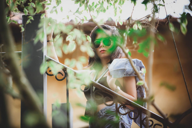 Portrait of young woman holding wearing sunglasses standing against railing