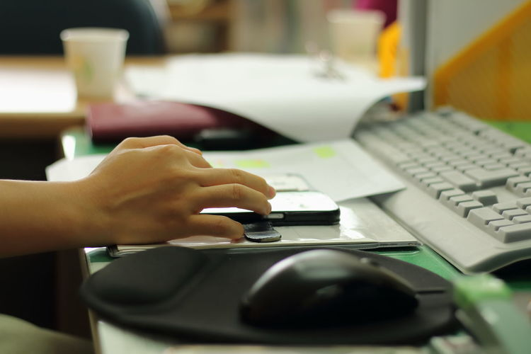 Cropped Hand Of Person Using Mobile Phone At Computer Desk