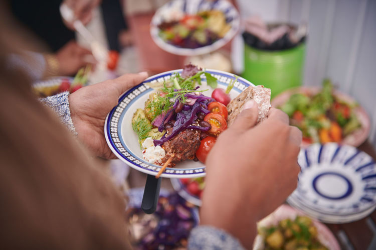 Midsection of people holding food
