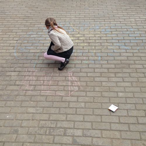 High angle view of girl drawing with chalk on footpath
