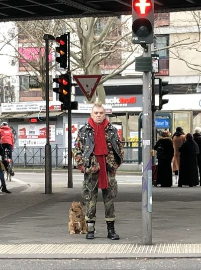 Full length of man with dog on street in city
