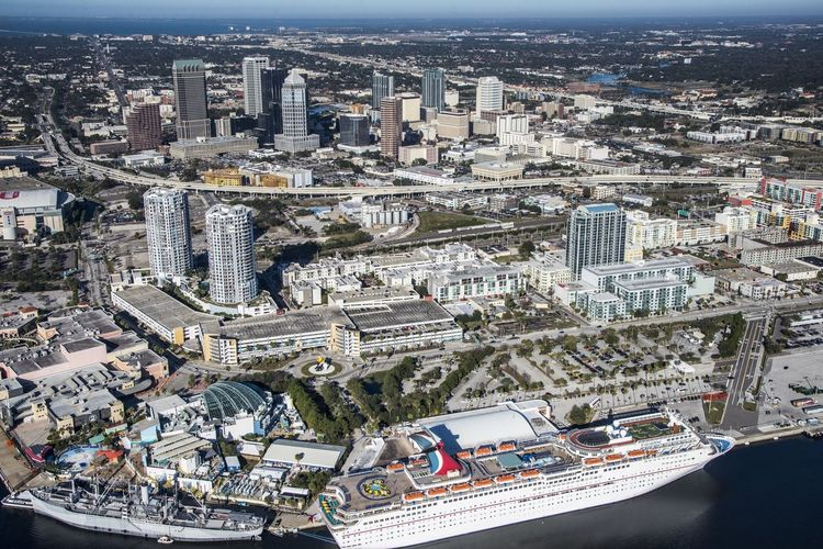 Aerial view of cruise ship and buildings in city on sunny day