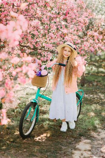 Woman standing by pink flowering tree