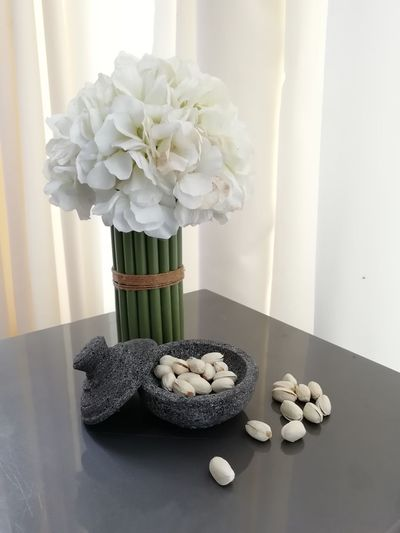 Close-Up Of Pistachios By Flowers In Vase On Table