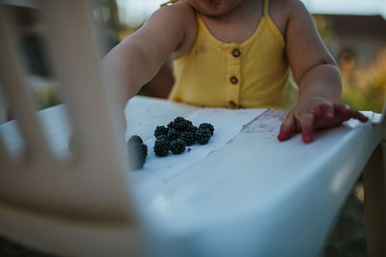 Midsection of baby girl with blackberries on table