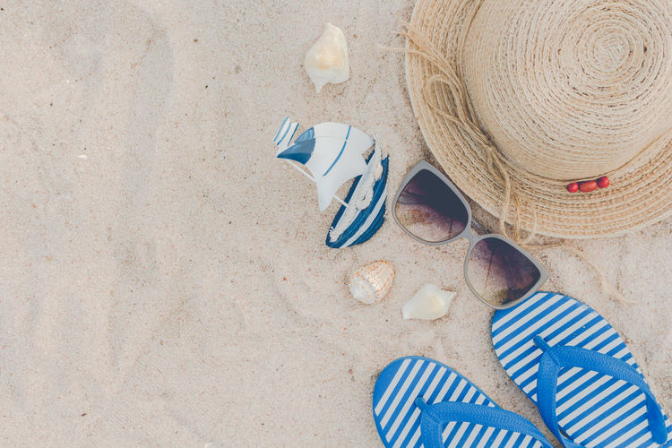 Straw hat and flip flops on a tropical beach Beach Blue Clothing Day Hat High Angle View Holiday Land Nature No People Outdoors Personal Accessory Sand Sandal Shell Shoe Slipper  Still Life Striped Summer Sun Hat Trip Vacations
