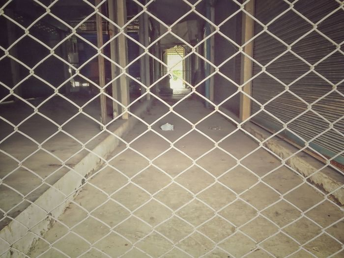 High angle view of chainlink fence against wall