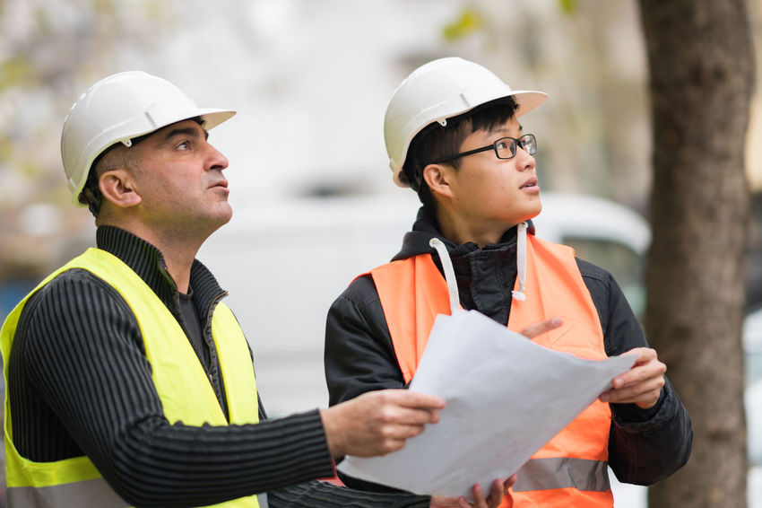 Construction site manager working with his young Asian apprentice Architecture Working Apprentice Apprenticeship Asian Man Caucasian Male Engineer Engineering Hardhat  Headwear Helmet Men Occupation People Person Protective Workwear Reflective Clothing Team Teamwork Trainee