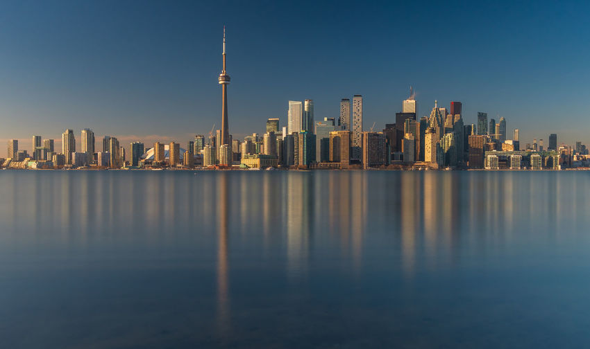 Long exposure daytime capture of the Toronto skyline Building Exterior Architecture Office Building Exterior Skyscraper Built Structure City Urban Skyline Waterfront Water Tall - High Cityscape Landscape Modern Travel Destinations Reflection Toronto Long Exposure Blue Daytime Modern Architecture