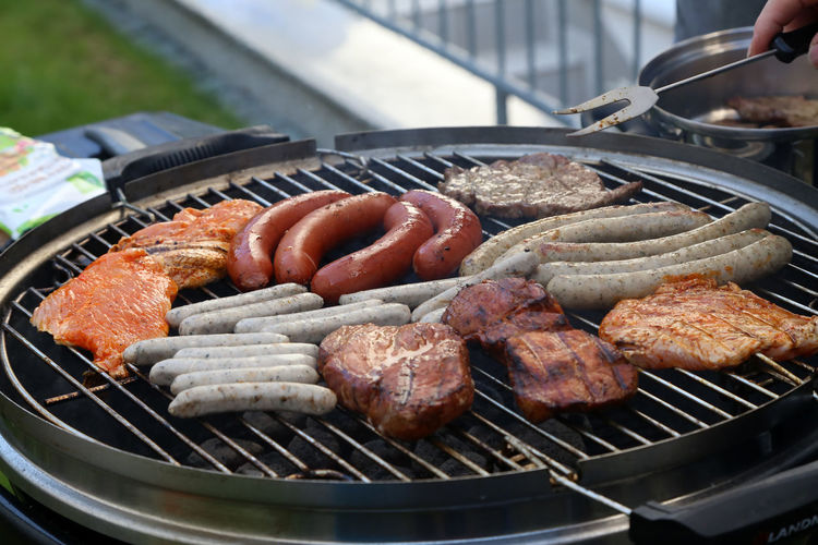 Barbecue Meat Food Food And Drink Barbecue Grill Freshness Preparation  Grilled Sausage Heat - Temperature Day Metal Close-up Preparing Food Serving Tongs Kitchen Utensil Outdoors Focus On Foreground Human Hand High Angle View Temptation Coal BBQ