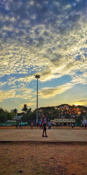 People playing soccer field against sky during sunset