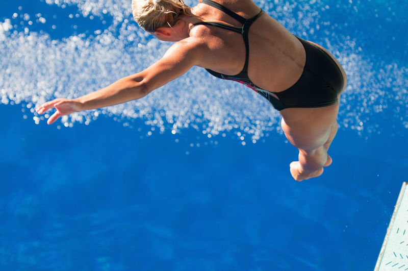 Spring Board Diver Takes A Leap 20s Athlete Blonde Copy Space Diving Jump Spring Board Springboard Jumping Sunlight Swiming Water Sport Blue Caucasian Dive Outdoors Spring Board Springboard Springboard Diver Summer Swimming Pool Underwater Unusual Angle Water Women Young Women