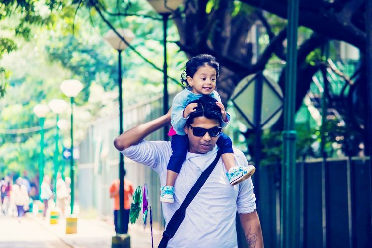 Man carrying daughter on shoulders while walking on footpath