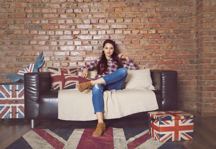 Portrait of woman sitting on sofa against brick wall