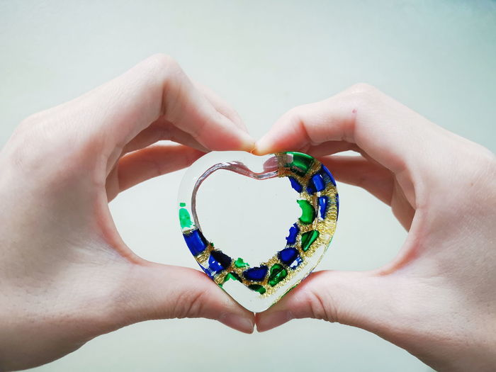 Close-up of hands holding heart shape decoration against wall