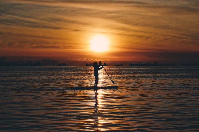 Silhouette of woman paddleboarding at sunset