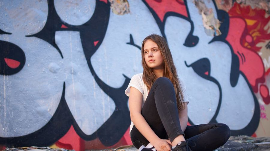 Full length of teenage girl sitting against graffiti wall