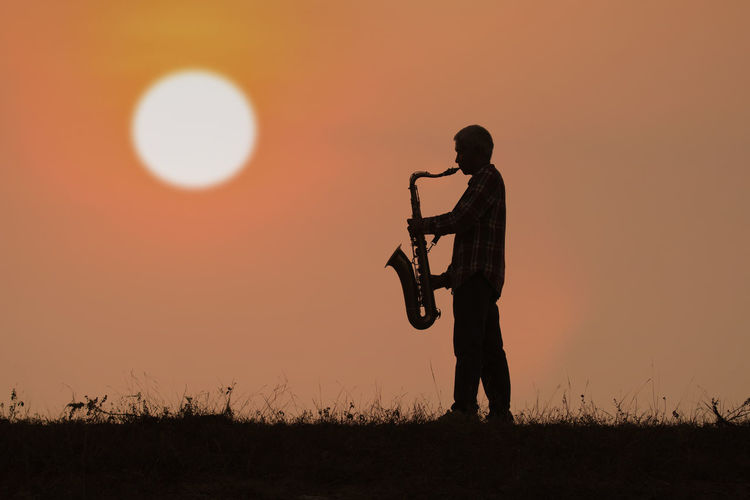 Man play saxophone with sunset or sunrise background Man Saxophone Playing Sun Sunset Sunlight Silhouette