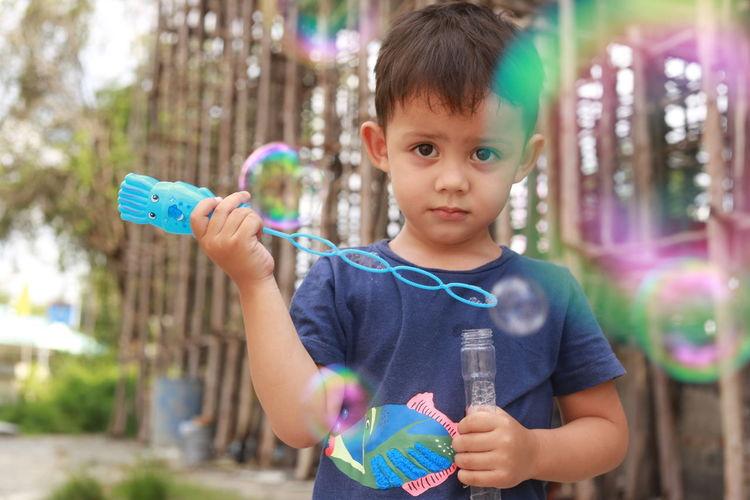 Portrait of cute boy holding bubbles