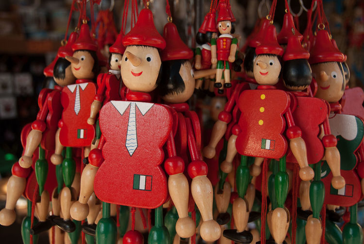 Pinocchio Pinocchio Red Toy Human Representation Childhood Creativity Male Likeness Art And Craft Retail  Figurine  Large Group Of Objects For Sale Hanging Puppet Puppets With A String Disney Red Hair Fairy Tale Fairy Tales Market Italy
